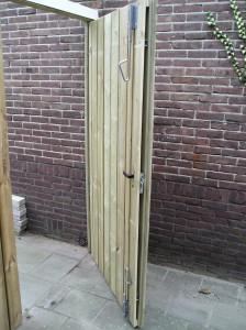 Poort van geimpregneerde planken. Deuren op een metalen frame